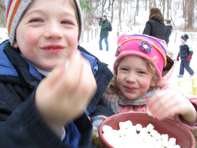 Leo and Sabine stealing marshmellows from the hot chocolate table