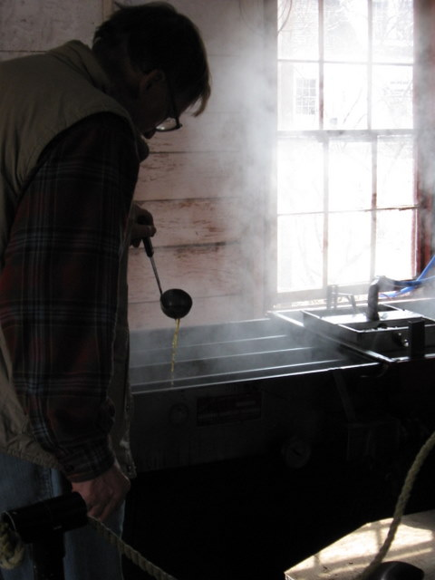 Showing off the amber syrup in the sugar shack